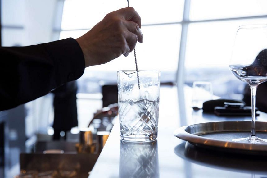 A bartender mixes up a martini at American Airlines' Flagship First Dining outlet. PHOTO: BLOOMBERG