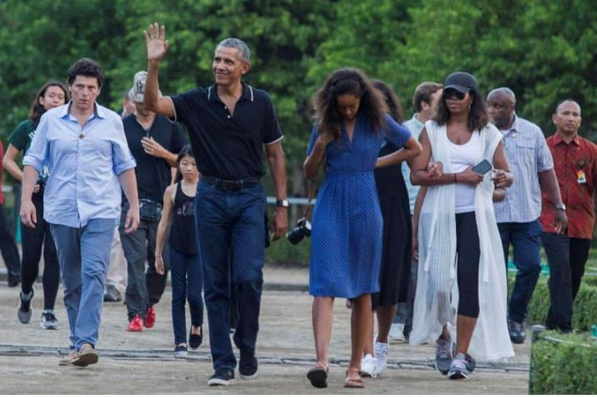 Former US President Barack Obama waves while walking with his daughter Malia and his wife Michelle during a visit to the 9th-century Borobudur Temple in Magelang, Indonesia, on June 28, 2017.