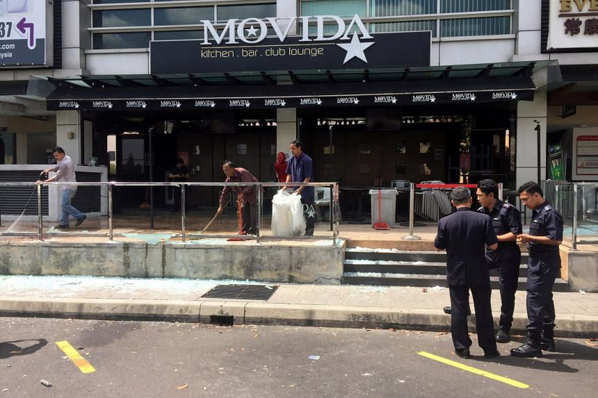 Police officers conducting investigations outside the Movida bar in Puchong, following a grenade attack, on June 28, 2016.