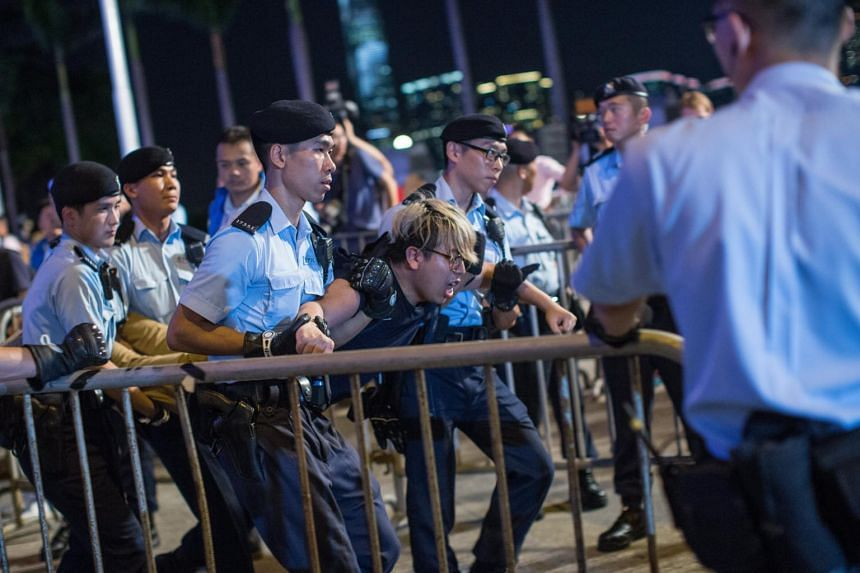 A protester is arrested by police after climbing on the Golden Bauhinia statue during a protest in Golden Bauhinia Square in Hong Kong, China, on June 28, 2017.