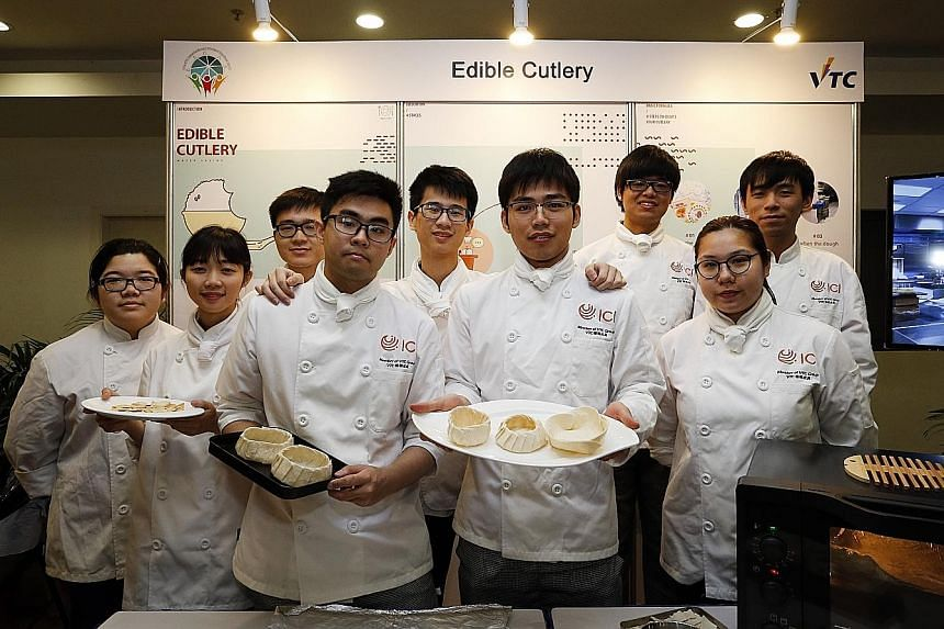 Nine graduates from Hong Kong's International Culinary Institute, led by Mr Raymond To (holding white plate), exhibiting their Edible Cutlery project at ITE College West yesterday.