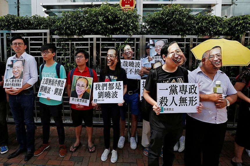 Supporters of Mr Liu Xiaobo, some wearing masks bearing his face, protesting outside China's Liaison Office in Hong Kong yesterday.