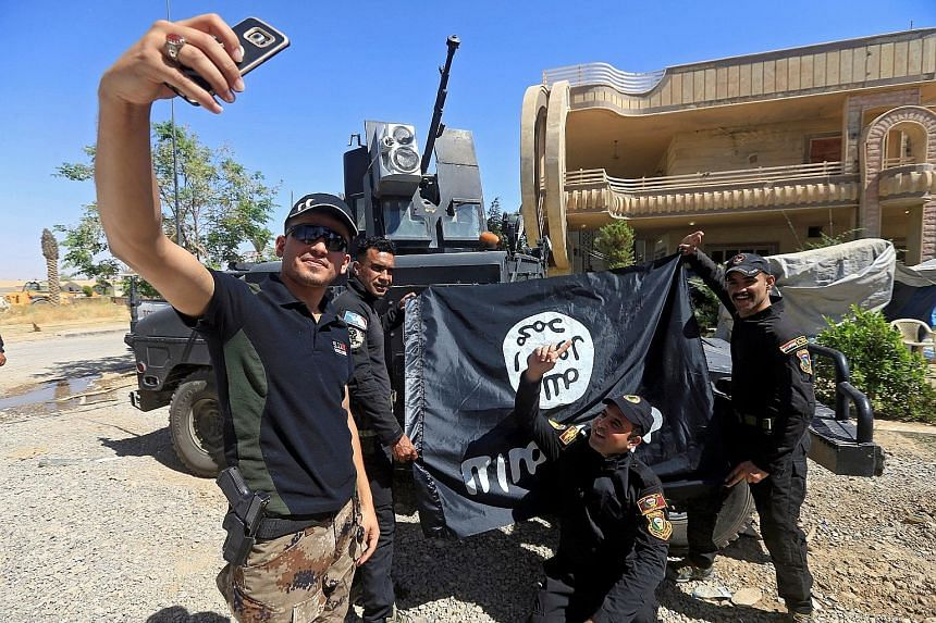 """Iraqi army soldiers taking a selfie with an ISIS flag, claimed after fighting with ISIS militants in western Mosul on Monday. The fall of Mosul would mark the end of the Iraqi half of the """"caliphate"""" proclaimed by ISIS though the terror group remains"""