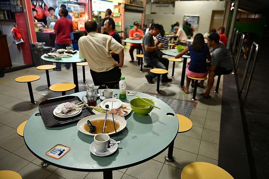 """Used plates and cutlery left behind by customers at a hawker centre at Block 210, Toa Payoh Lorong 8, yesterday. Findings from the Graciousness Survey released yesterday showed that people rated Singapore 5.52 for """"cleaning up after meals in public s"""