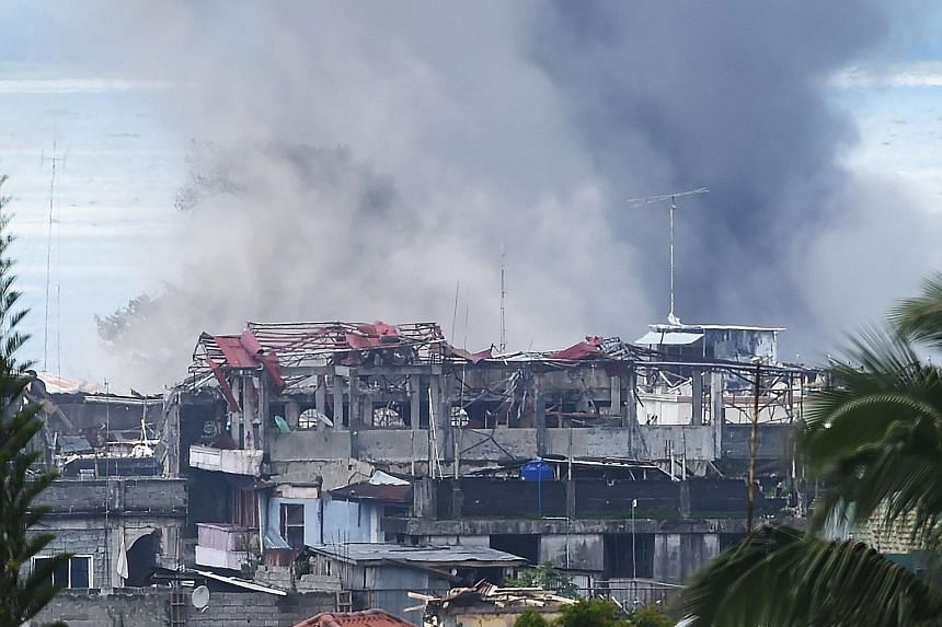 Smoke billowing from burning houses after aerial bombing by the Philippine Air Force on militant Islamist positions in Marawi yesterday.