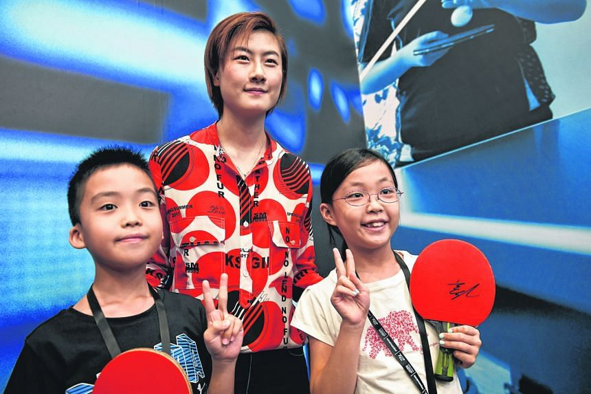 World No. 1 Ding Ning, posing with young fans Kok Cern Hann, 11 (left), and his sister, Kok Yi Mun, nine, at yesterday's curtain-raiser for the T2 Asia Pacific Table-tennis League. Ding says the 24-minute limit for matches will have a direct bearing on mo