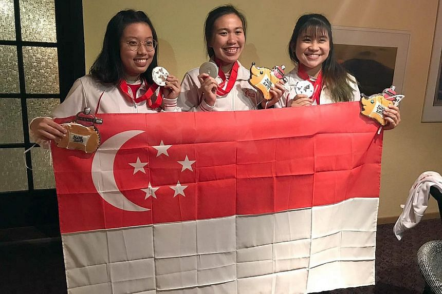 Singapore shooters (from left) Adele Tan, Ho Xiu Yi and Martina Lindsay Veloso celebrating their silver.