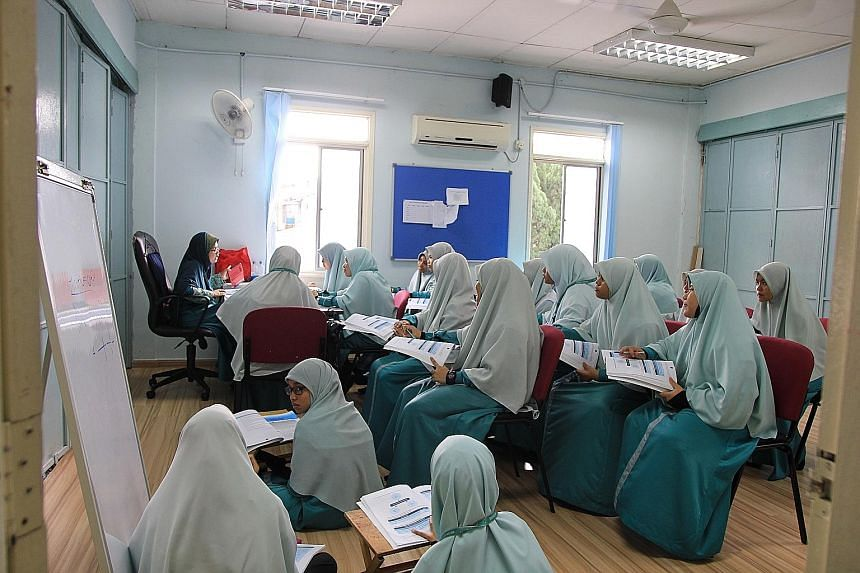 """Muslim girls at a tahfiz - which means """"memorising"""" (the Quran), where classes go on into the night. Below: Muslim boys at a religious school, many of which are in residential neighbourhoods. Many tahfiz schools do not provide a parallel system for s"""