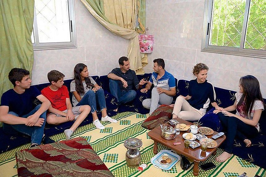 A handout photo released yesterday showing Syrian President Bashar al-Assad (centre) and (from left) his sons Hafez and Karim, daughter Zein and wife Asma visiting injured armed forces members in the central province of Hama.