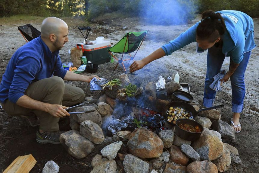 Married chefs John Griffiths and Leslie Peng tend to an elaborate meal near Wrights Lake in California's Sierra Nevada Mountains. PHOTO : NYTIMES