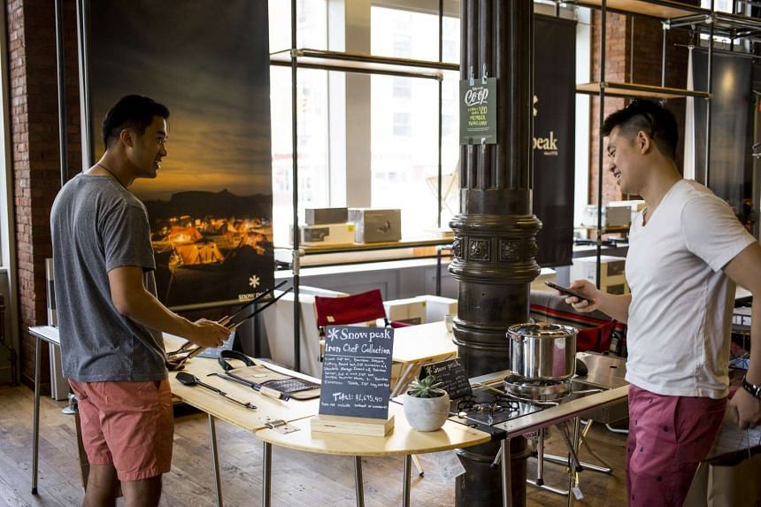 Customers browse camp-site cooking gear at a REI store in Manhattan. PHOTO: NYTIMES