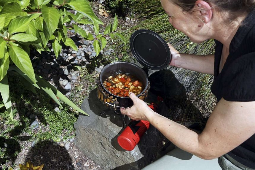 Laura Ohm heats up lamb bolognese, which was prepared at home, dehydrated and vacuum-sealed before a camping trip, in Portland, Oregon. PHOTO: NYTIMES