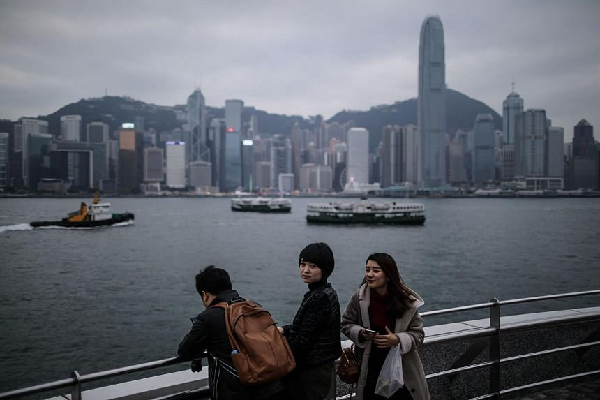 Mainland Chinese tourists visiting a viewing deck overlooking Victoria Harbour in Hong Kong on Dec 17, 2016.