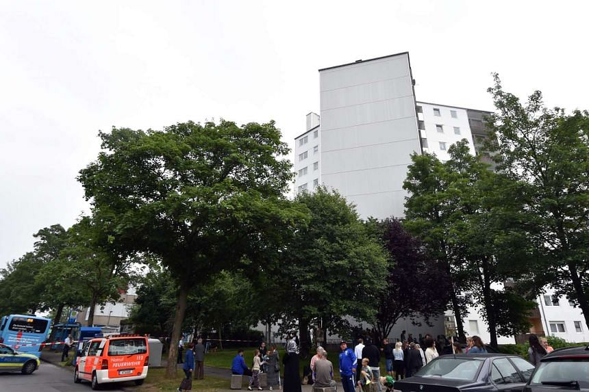 Residents stand in front of a building which was evacuated on June 27, 2017, in Wuppertal, Germany.
