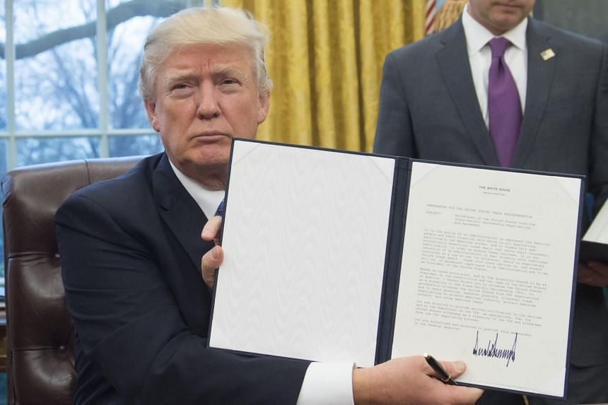 US President Trump holding up an executive order withdrawing the US from the Trans-Pacific Partnership after signing it, on Jan 23, 2017.