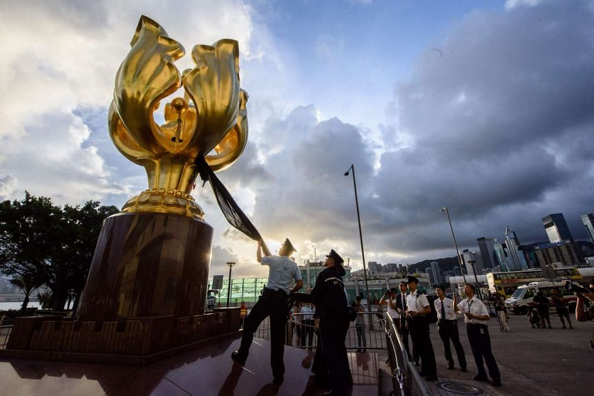Police remove a black cloth after Demosisto party members and democracy campaigner Joshua Wong took part in a protest to cover the Golden Bauhinia statue with a black cloth in Hong Kong on June 26, 2017, ahead of the 20th anniversary of the city's ha