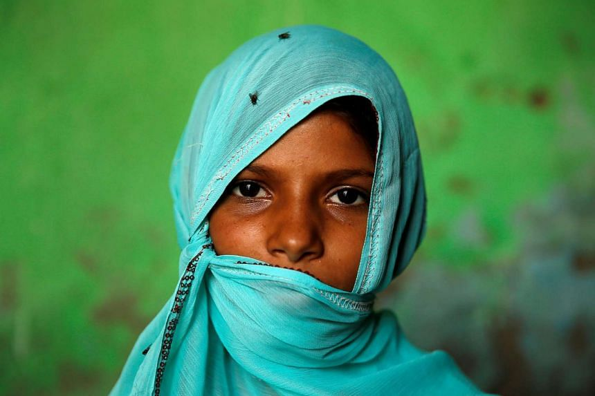A Muslim girl poses as she shelters from the sun in the village of Jaisinghpura in the northern state of Haryana, India, on June 2, 2017. An advertisement sponsored by the government of Haryana that featured the image of a woman, her face shrouded by