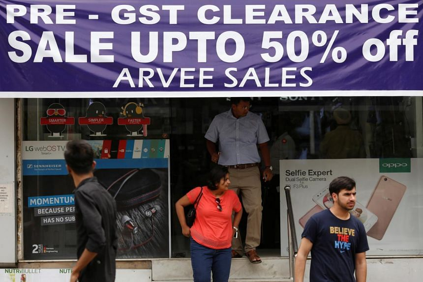 A banner promoting Goods and Services Tax clearance sale at an electronic shop in New Delhi.