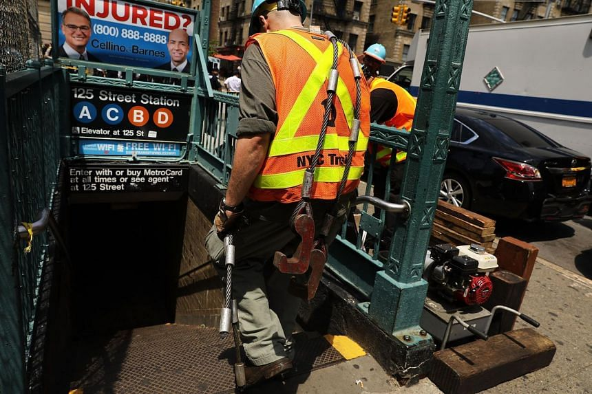 A Metropolitan Transportation Authority worker entering a Harlem subway station where a morning train derailment occurred, on June 27, 2017.