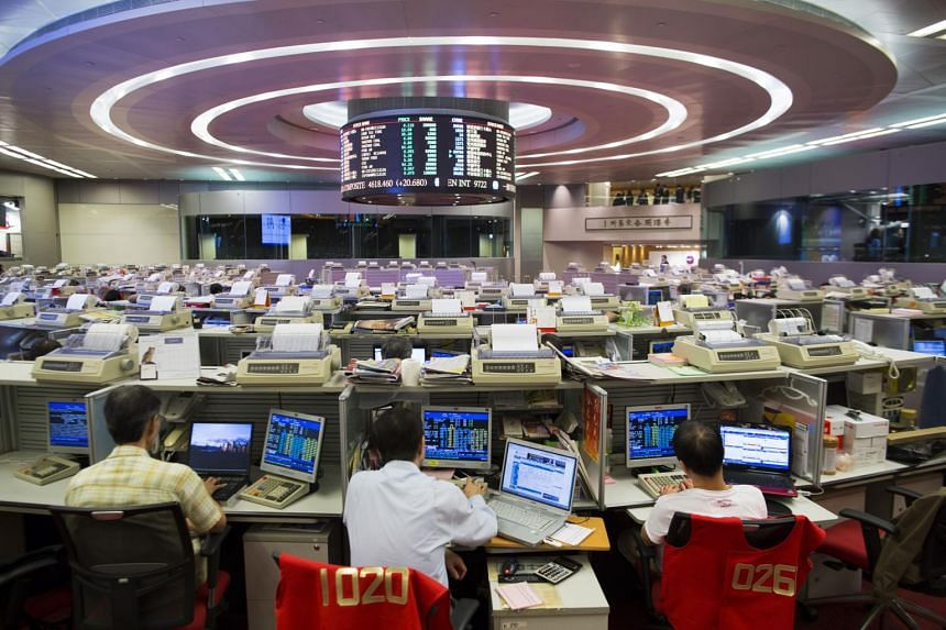 Stock traders at their desks facing an electronic board on the trading floor of the Hong Kong Stock Exchange.