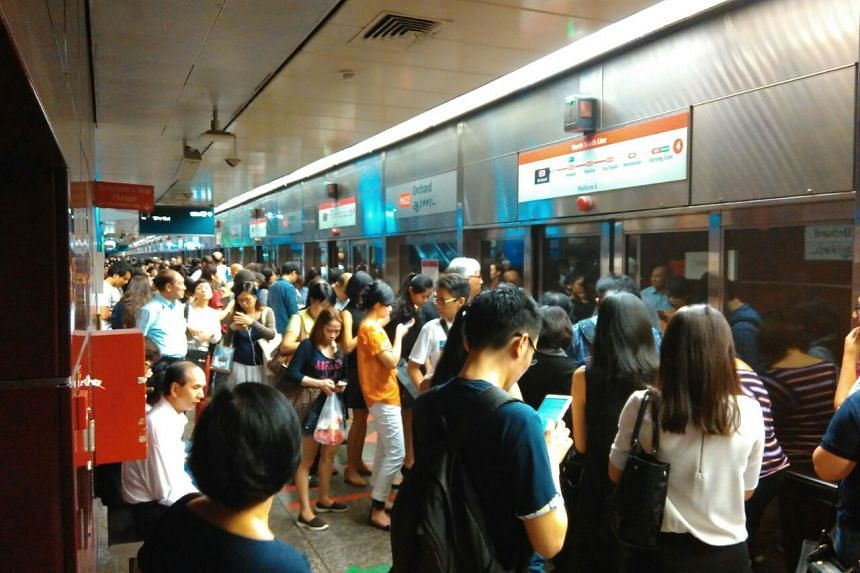 Commuters waiting for the train at Orchard MRT station.