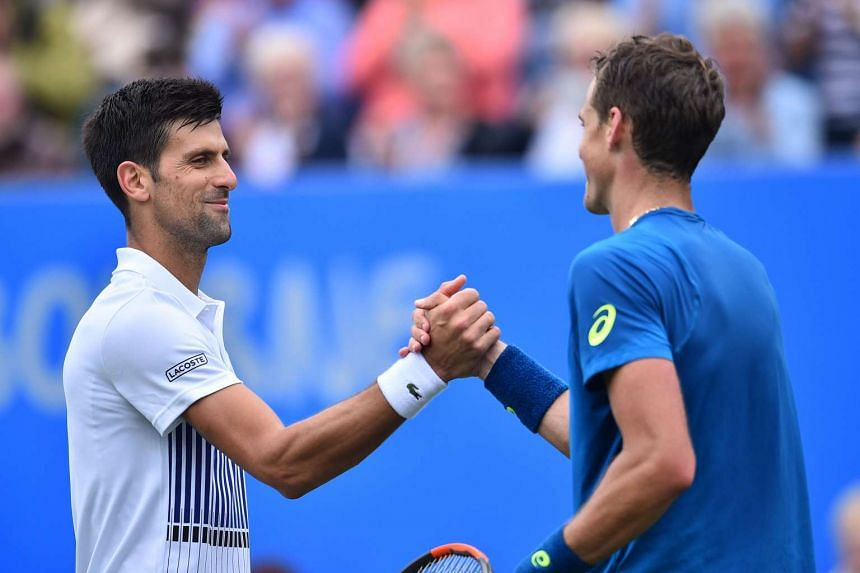 Djokovic (left) shakes hands with Canada's Vasek Pospisol after the match.