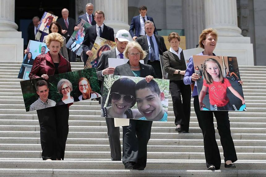 Senate Democrats walk down the Senate steps holding photos of people who would lose their health coverage.