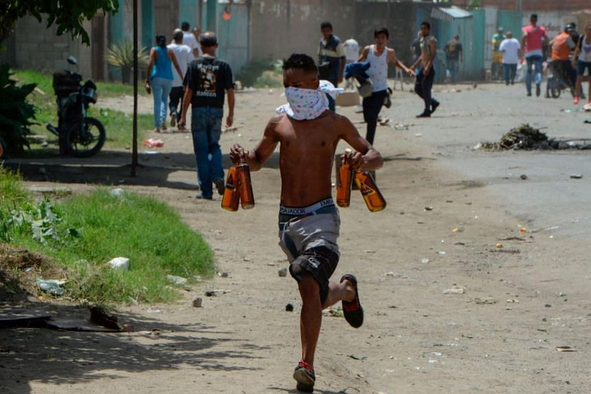 A young man runs carryng stolen alcohol bottles after looting a supermarket in Maracay, Aragua state, Venezuela on June 27, 2017.
