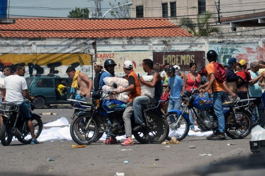 People mount their motorbikes carrying stolen food and supplies, after looting a supermarket in Maracay, Aragua state, Venezuela on June 27, 2017.