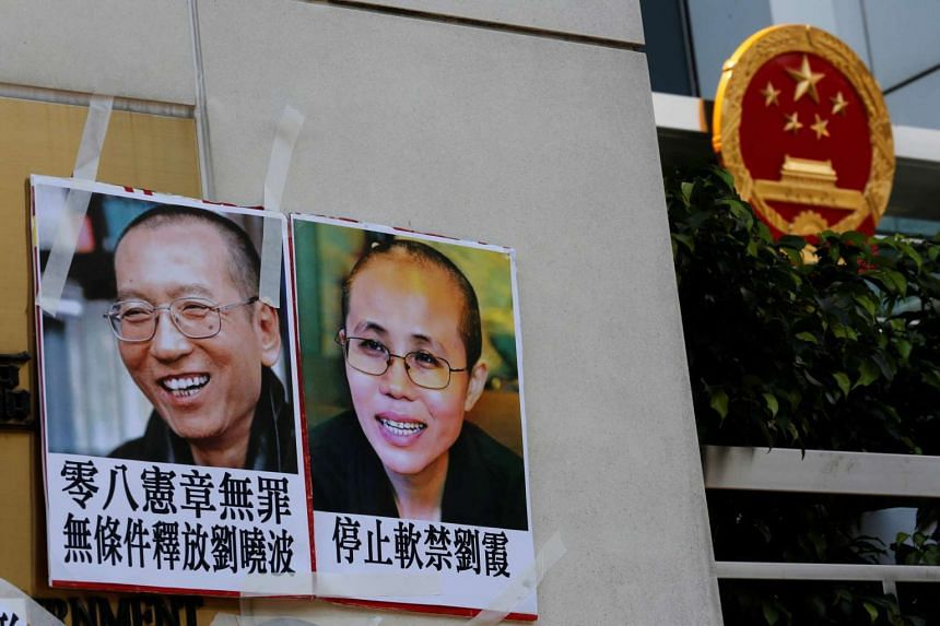Photos of Chinese Nobel rights activist Liu Xiaobo (left) and wife Liu Xia are seen outside the China Liaison Office in Hong Kong on June 27, 2017.