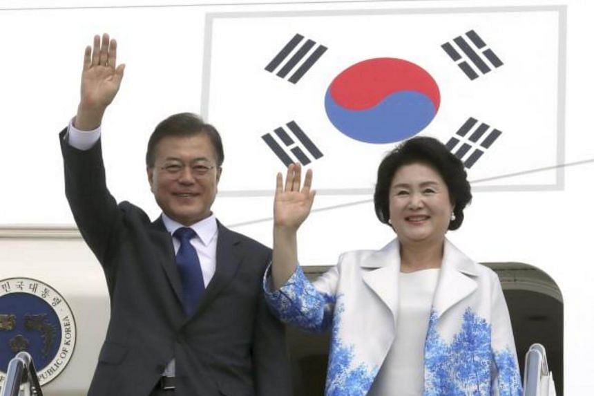 South Korean President Moon Jae In and his wife, Kim Jung Sook, wave after arriving at Joint Base Andrews in Washington, DC, USA, on June 28, 2017.