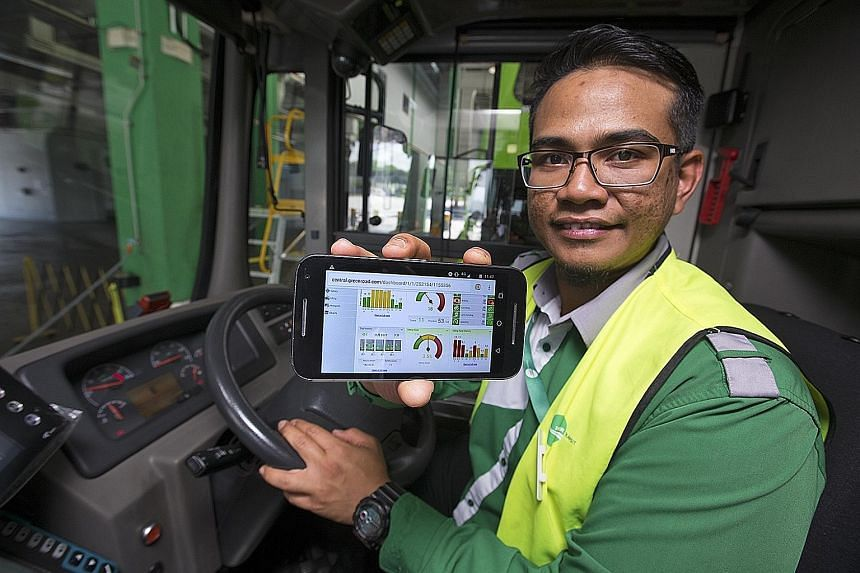 Tower Transit bus driver Amirul Hakim showing how his driving performance can be tracked and collated on a mobile phone app, which he can then review. A colour-coded panel in the bus will flash red, amber or green, according to the driver's driving p