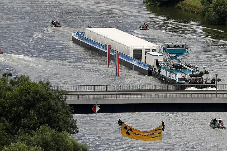 A ship with nuclear waste containers - or Castor containers - makes it way along the Neckar River in Bad Wimpfen, Germany, yesterday, as members of environmental organisation Robin Wood hang under a bridge to try and block it. It was the first of fiv