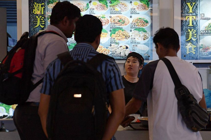 A noodle stall displaying a bilingual menu at a foodcourt in Nanyang Technological University (NTU).