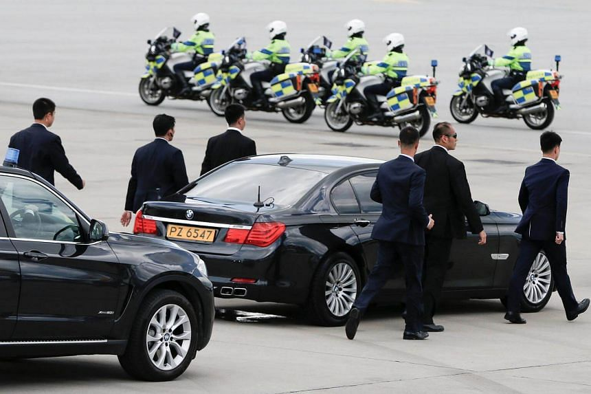 Bodyguards escort the car of Chinese President Xi Jinping after his arrival at the airport in Hong Kong, China, on June 29, 2017.