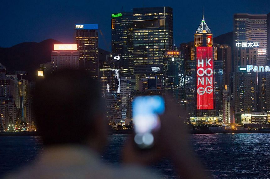 Tourists look out at the Victoria Harbour front as a light display commemorating the 20th anniversary of the city's handover from British to Chinese rule sits on a building ahead of Chinese President Xi Jinping's arrival in Hong Kong, sits on a build