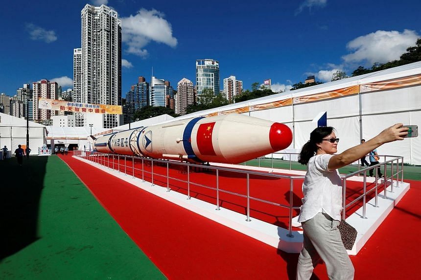 A woman takes a selfie in front of a Changzheng-1 (CZ-1) or Long March 1 rocket displayed at a high-tech fair, to celebrate the 20th anniversary of the territory's handover to Chinese rule, in Hong Kong, on June 28, 2017.