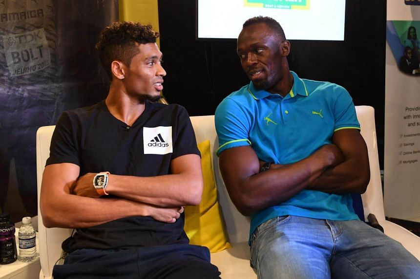 Usain Bolt of Jamaica (right) chats with Wayde Van Niekerk of South Africa during a press conference in Kingston, on June 8, 2017.