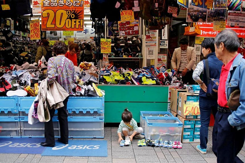 A child reaches for a pair of shoes at a shoe store on a shopping street in Tokyo.