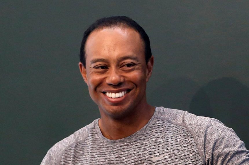 Golfer Tiger Woods smiles as he sits down to sign copies of his book, The 1997 Masters: My Story at a Barnes & Noble store in New York City.