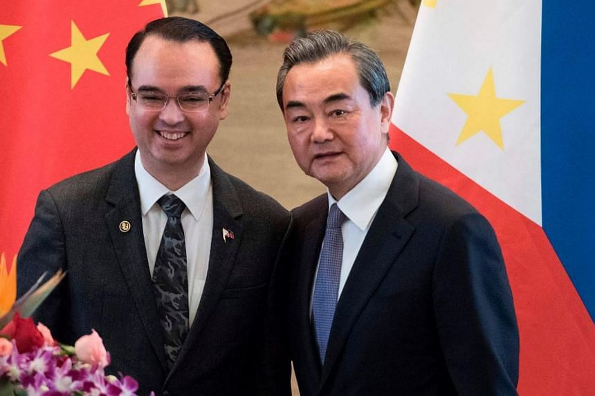 Chinese Foreign Minister Wang Yi (right) poses with Philippines Department of Foreign Affairs (DFA) secretary Alan Peter Cayetano at the end of a press conference at the Ministry of Foreign Affairs in Beijing on June 29, 2017.