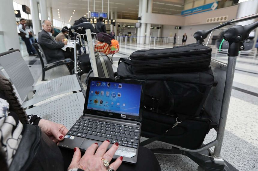 A Syrian woman opens her laptop before checking in at Beirut international airport, in March 2017.