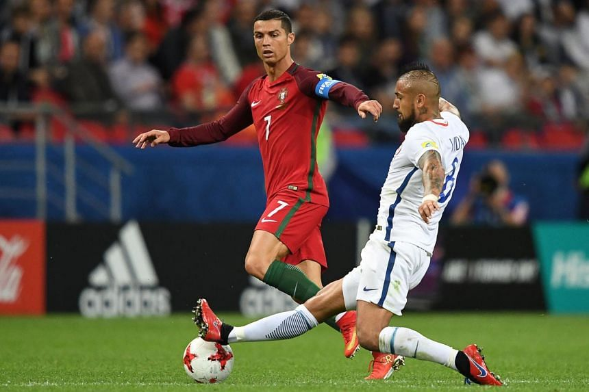 Portugal's forward Cristiano Ronaldo fighting for the ball against Chile's midfielder Arturo Vidal during the 2017 Confederations Cup semi-final football match between Portugal and Chile at the Kazan Arena in Kazan on June 28, 2017.