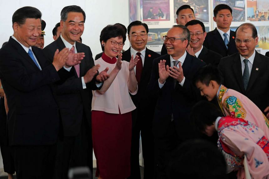 (From left) Chinese President Xi Jinping, Hong Kong Chief Executive Leung Chun-ying, and Chief Executive-elect Carrie Lam applauding after watching two Chinese opera performers during a visit to Hong Kong's West Kowloon district on June 29, 2017.