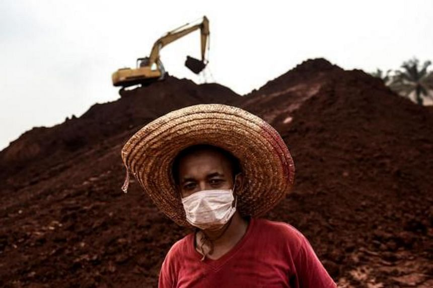 A worker wearing a face mask looks on at a bauxite storage site in Bukit Goh situated in Malaysia's rural state of Pahang on Oct 13, 2015.