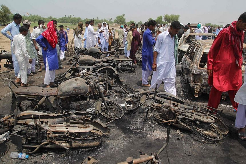 Pakistani villagers gathering at the site of a deadly oil tanker fire following an accident in the town of Ahmedpur East on June 26, 2017.