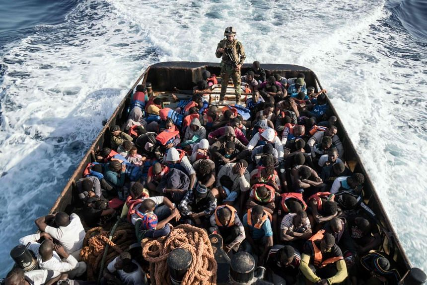 A Libyan coastguard stands on a boat during the rescue of 147 illegal migrants attempting to reach Europe.