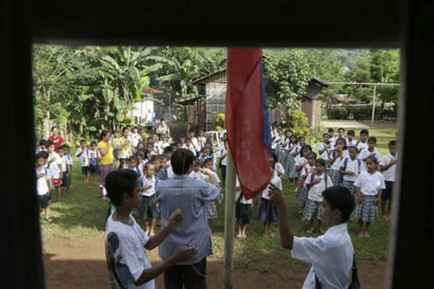 Elementary pupils sing the Philippine national anthem during a flag-raising ceremony.