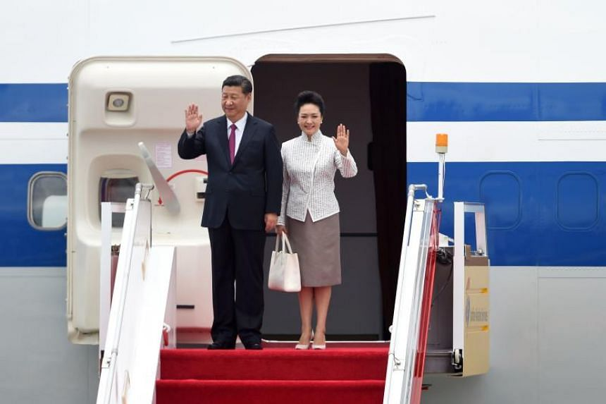 China's President Xi Jinping (left) and his wife Peng Liyuan wave upon their arrival at Hong Kong's international airport on June 29. The Chinese president is in Hong Kong to mark 20 years since it was handed back to China by Britain, with leading de