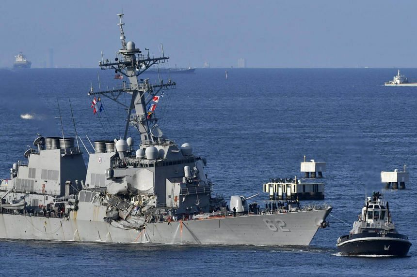 A tugboat pulls the US Navy destroyer USS Fitzgerald as it arrives at Yokosuka Naval Base after its collision with the container ship ACX Crystal off the coast of Yokosuka, Japan, on June 17, 2017.
